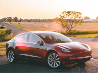 red tesla car parked with field scenery in background